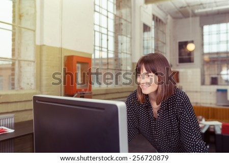Smiling businesswoman working alone at a large screen desktop computer in a spacious office with a smile on her face - stock photo