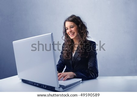 Smiling businesswoman working on a laptop - stock photo