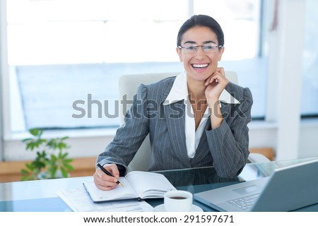 Smiling businesswoman working with her laptop and writing notes in an office