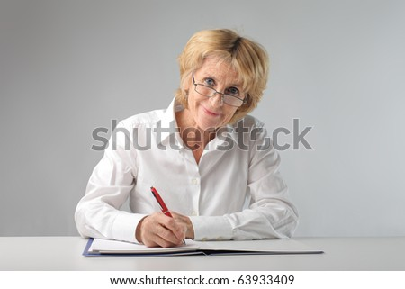 Smiling businesswoman writing on a register - stock photo
