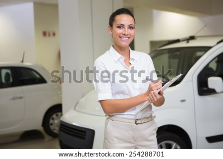 Smiling businesswoman writing on clipboard at new car showroom - stock photo