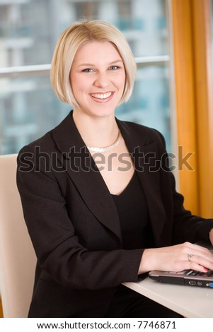 smiling businesswomen and laptop
