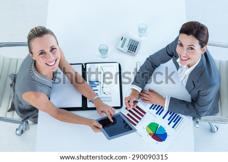 Smiling businesswomen working together in an office - stock photo
