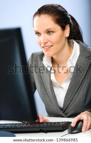 Smiling busy businesswoman working on her computer - stock photo