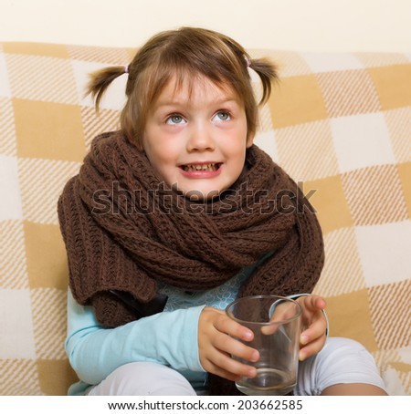 Smiling but ill child dressed in warm scarf drinking from glass on couch. - stock photo