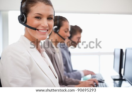 Smiling call center agent with working colleagues behind her - stock photo