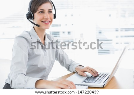 Smiling call center agent working at desk with headset and laptop