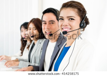 Smiling call center (or telemarketer) team - customer service operator concept