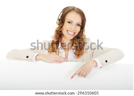 Smiling call center woman pointing empty banner. - stock photo