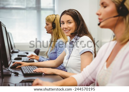 Smiling call centre agent talking on the headset in the office - stock photo