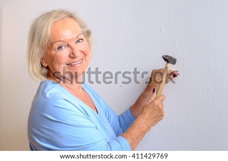 Smiling capable elderly woman doing DIY standing holding a nail and hammer as she prepares to knock it into a wall, upper body isolated on white