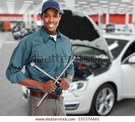 Smiling car mechanic with wrench in auto repair service.  - stock photo