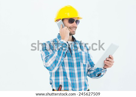 Smiling carpenter using digital tablet and cellphone against white background - stock photo