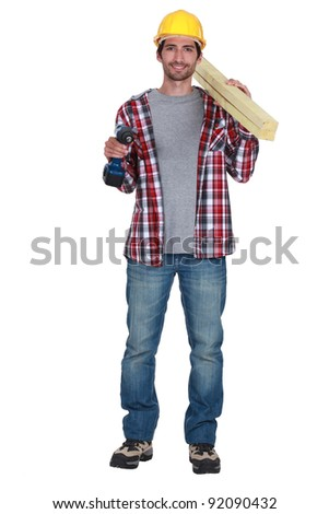 Smiling carpenter with drill and planks - stock photo