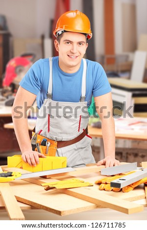 Smiling carpenter working in a workshop - stock photo