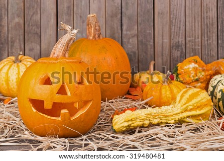 Smiling carved autumn pumpkin on a straw and wood background - stock photo