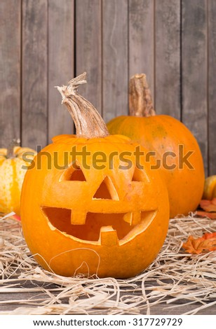 Smiling carved autumn pumpkin on a wood background - stock photo