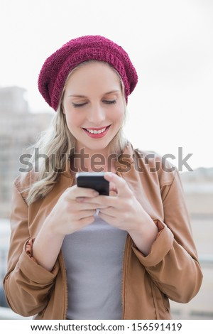 Smiling casual blonde text messaging outdoors on urban background - stock photo