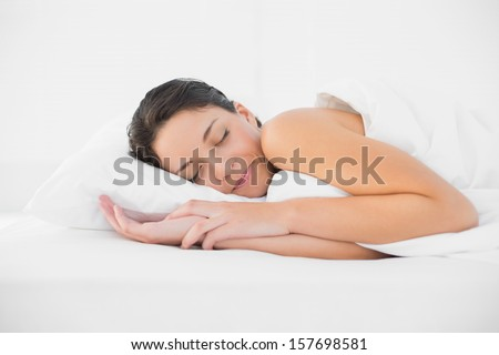 Smiling casual brunette sleeping in her bed in bright bedroom - stock photo