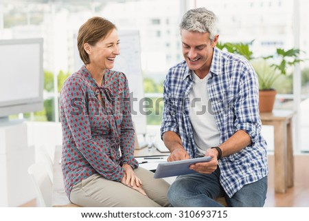 Smiling casual business colleagues using tablet in the office - stock photo