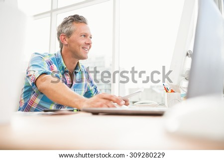 Smiling casual designer working with computer in the office - stock photo
