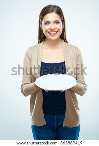 Smiling casual dressed woman hold empty plate. White background isolated. - stock photo