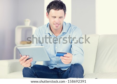 Smiling casual man using tablet and credit card in bright living room