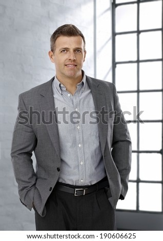 Smiling casual mature businessman in gray jacket looking at camera. - stock photo