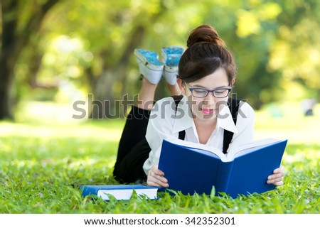 Smiling casual student lying on grass reading book - stock photo