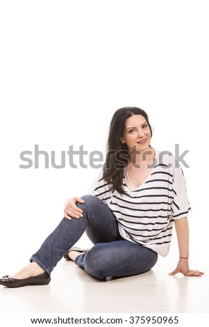 Smiling casual woman sitting on floor against white background - stock photo
