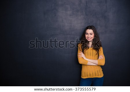 Smiling casual woman standing with arms folded over black background - stock photo