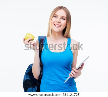Smiling casual woman with backpack holding green apple and tablet computer. Standing isolated on a white background. Looking at camera - stock photo