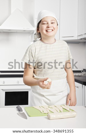 Smiling caucasian boy holding raw croissant made by himself while standing at the kitchen - stock photo