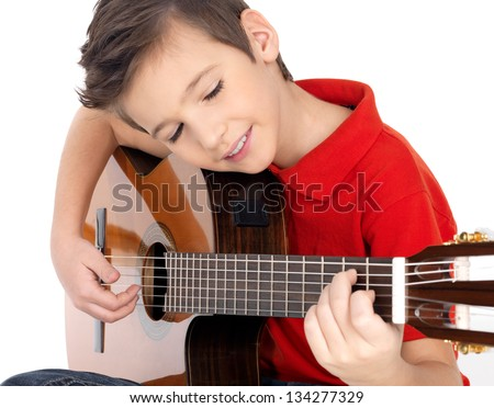 Smiling caucasian boy is playing the acoustic guitar - isolated on white background - stock photo