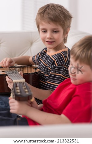 Smiling caucasian boy playing acoustic guitar. boys sitting on couch and adjusting strings - stock photo