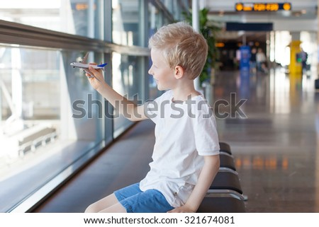 smiling caucasian boy playing with toy plane in the airport waiting for travel departure - stock photo