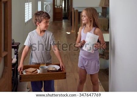 Smiling caucasian brother and sister siblings carrying surprise mothers day breakfast tray - stock photo