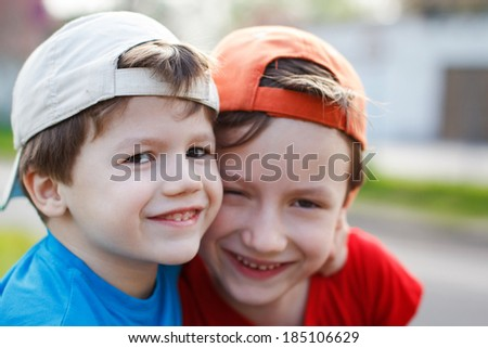 Smiling caucasian brothers in cap, outdoor portrait - stock photo
