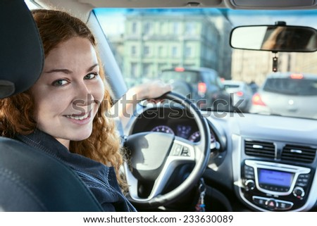 Smiling Caucasian brunette driving car, looking back at camera - stock photo