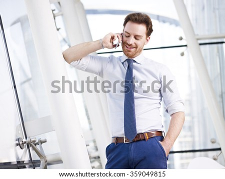 smiling caucasian business executive talking on mobile phone in modern office building. - stock photo