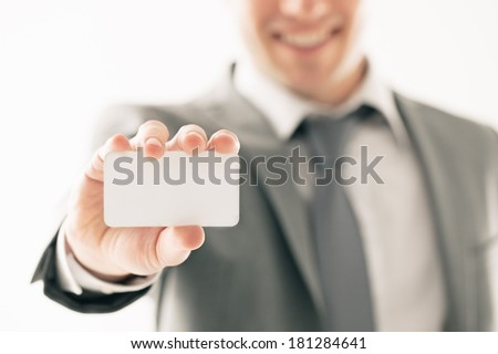 Smiling Caucasian businessman holding a blank business card in his hand. - stock photo