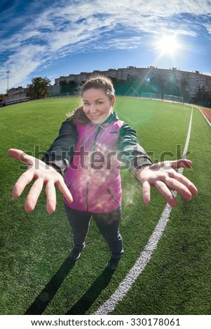 Smiling Caucasian cheerful sportswoman stands on green playing field against sun, showing palm up, full-length portrait - stock photo