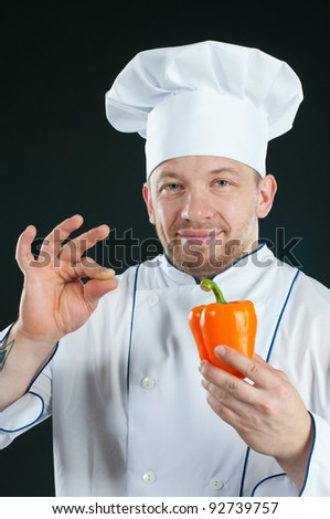 Smiling caucasian chef with bell pepper gesturing OK, over dark background - stock photo