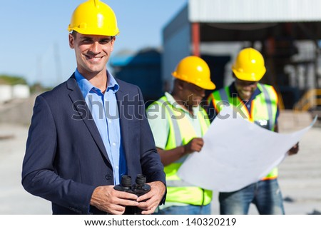 smiling caucasian construction supervisor with binoculars - stock photo