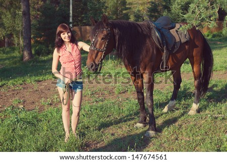 Smiling caucasian female with a brown horse on a summer evening - stock photo