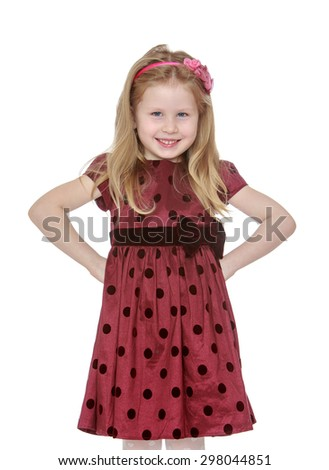 Smiling Caucasian girl with long hair which keeps the headband in Burgundy polka dot dress stands in front of the camera, hands on hips , close-up-Isolated on white - stock photo