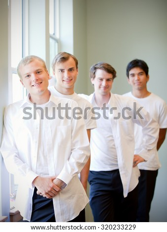 Smiling Caucasian groom standing by window with groomsmen, getting ready for wedding - stock photo