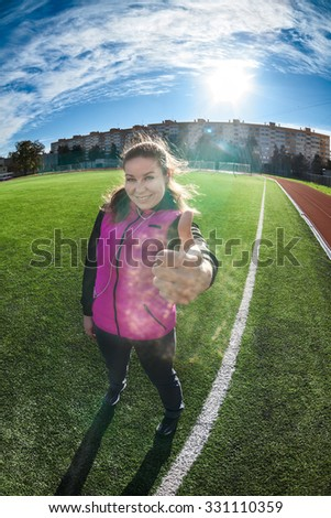 Smiling Caucasian happy sportswoman stands on green playing field against sun, showing thumb up, full-length portrait - stock photo