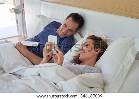 smiling caucasian husband and wife couple lying on the bed using tablet device and smartphone in morning weekend - stock photo