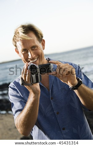 Smiling Caucasian male video recording at the beach. Vertical format.